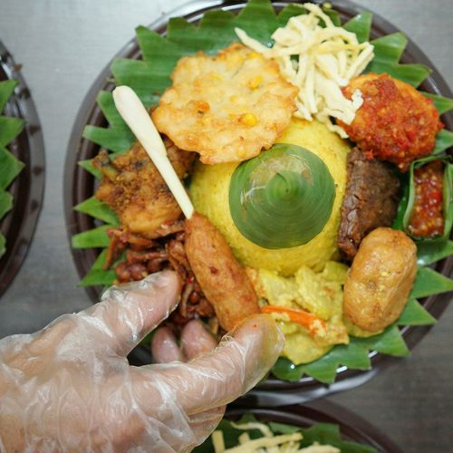 Cropped Image Of Hand By Food In Plate On Table