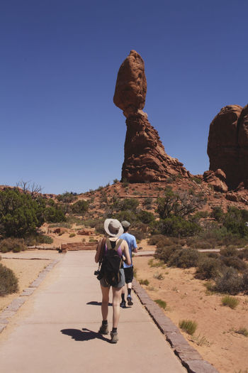Rear view of friends walking on rock