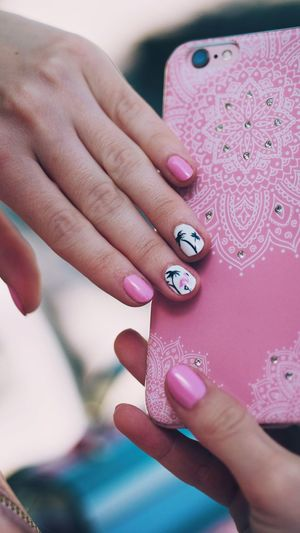 Close-Up Of Woman With Nail Polishes Holding Smart Phone