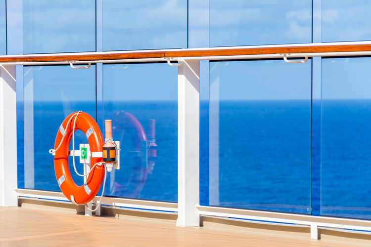 Railing by sea against blue sky seen through window