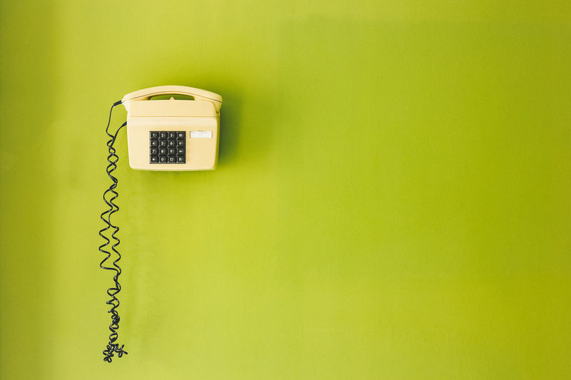 Close-up of telephone booth on green wall