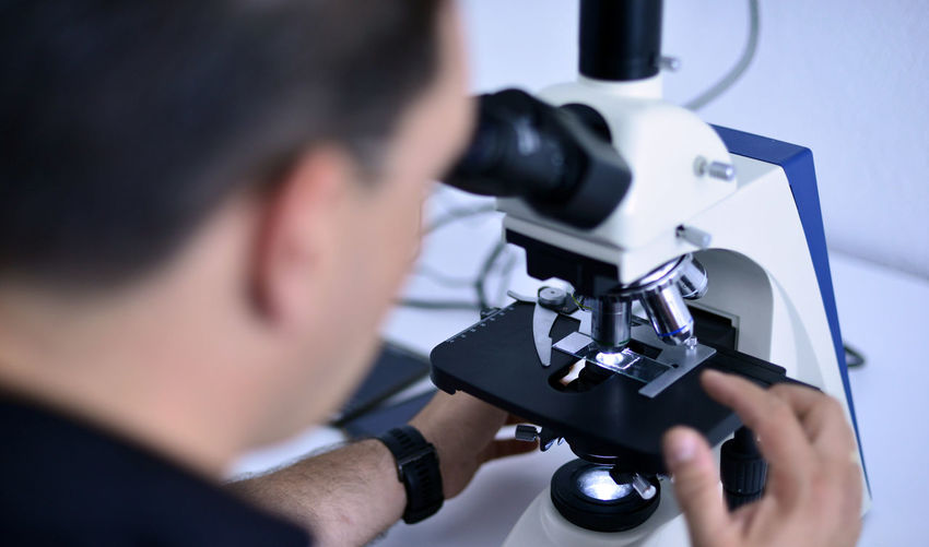Close-Up Of Male Scientist Looking Through Microscope At Laboratory