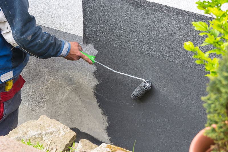 Close-up, arm of a house painter with paint roller in hand painting a house wall with gray paint. Adult Adults Only Architecture Building Exterior Close-up Day Holding Human Body Part Human Hand Men One Man Only One Person Only Men Outdoors People Protective Glove Spraying Standing