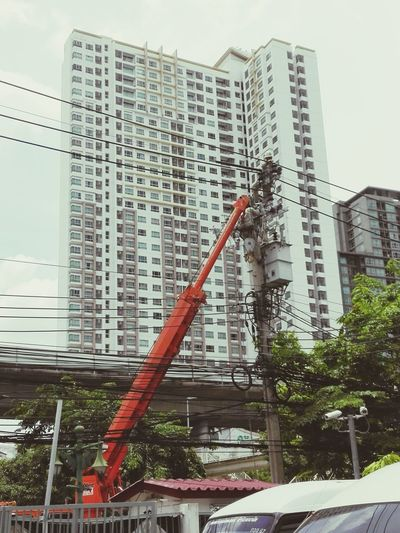 Low angle view of cherry picker against skyscraper
