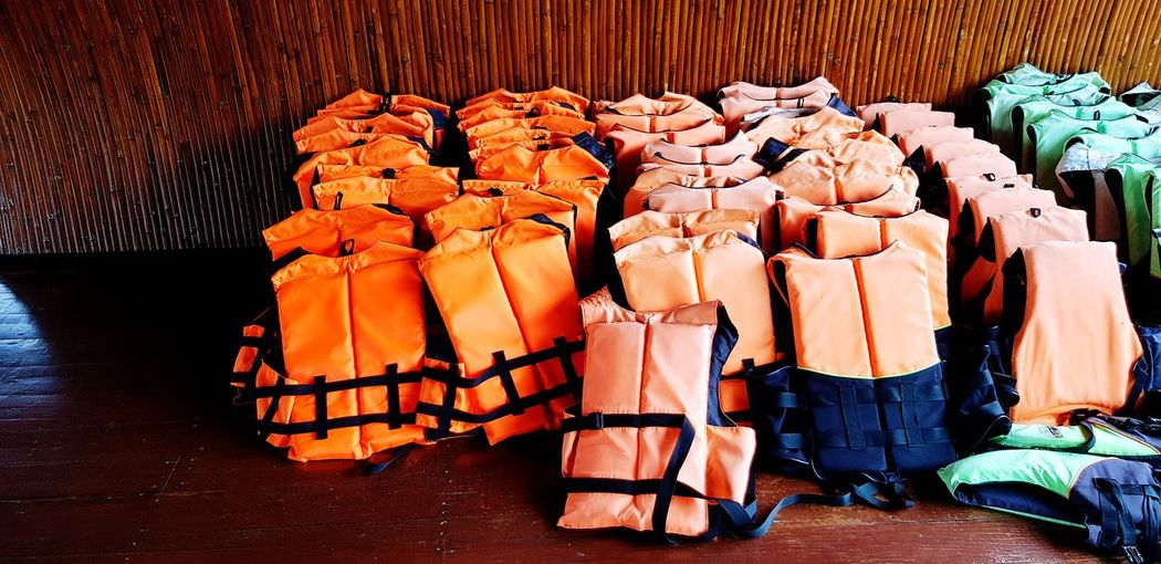 Safety life suit Rescue Color Colorful Beach RENT Life Protection Protect Sport Activity Swimming Orange Green Wood - Material Wearing Life Jacket Life Vest Safety Safe Swimmer Water EyeEm Selects EyeEmNewHere Stack Shop Wooden For Sale Retail Display Collection