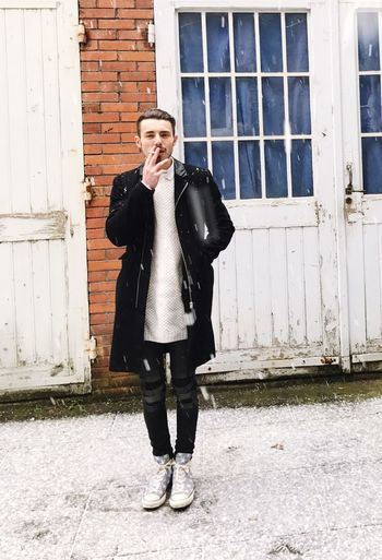 Young man smoking while standing outside house during snowfall