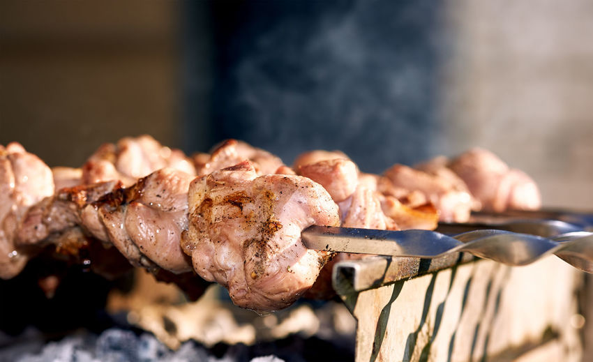 Close-up of meat in skewer on barbecue at back yard