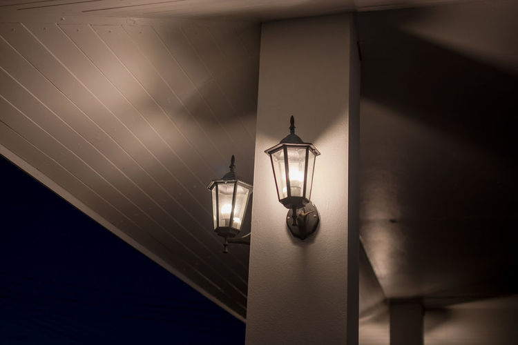Low angle view of illuminated light bulb hanging on ceiling