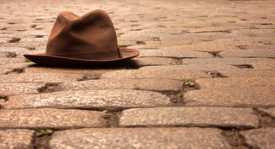 Close-Up Of Brown Fedora Hat On Cobblestone Street