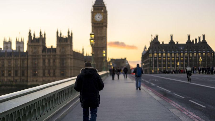 Rear view of man walking westminster bridge against big ben