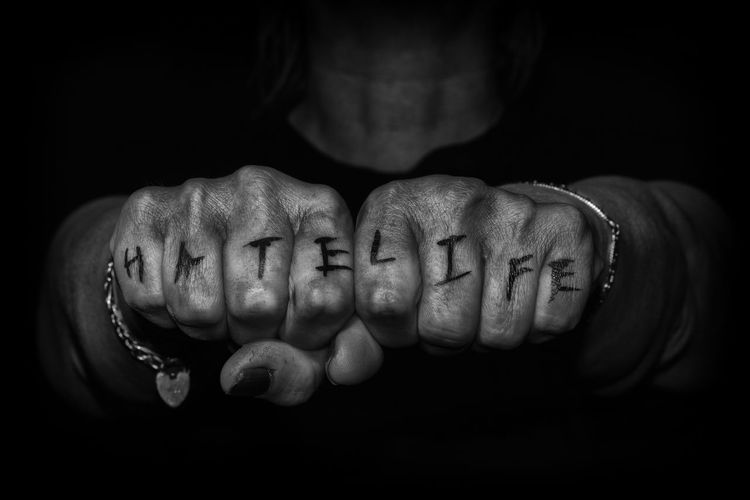 Close-up of fists with text against black background