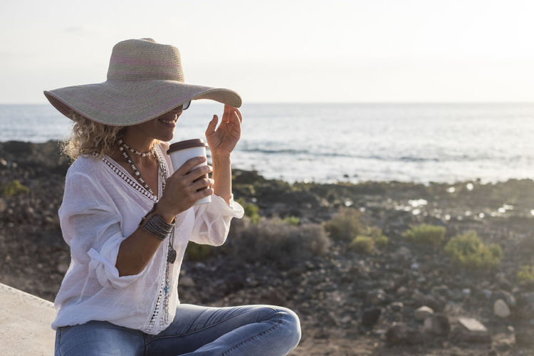 Beautiful woman with hat drinks a coffee in relax along the beach. Horizon over water Sea Water Leisure Activity Hat Real People Land Casual Clothing Lifestyles Three Quarter Length Beach Clothing Sitting Nature Day Women People Beauty In Nature Adult Scenics - Nature Horizon Over Water Outdoors Holiday Summer Drinking Coffee Enjoying Life Relaxation Coastline Rocks Volcanic Landscape Ocean Island Beautiful Woman Smiling Sunset Sunlight One Person Hippie Happiness Caucasian