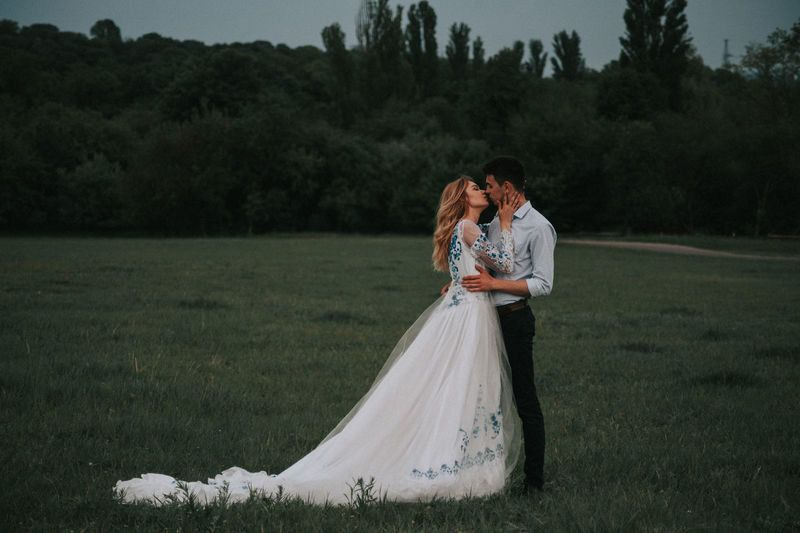 Couple kissing while standing on grass