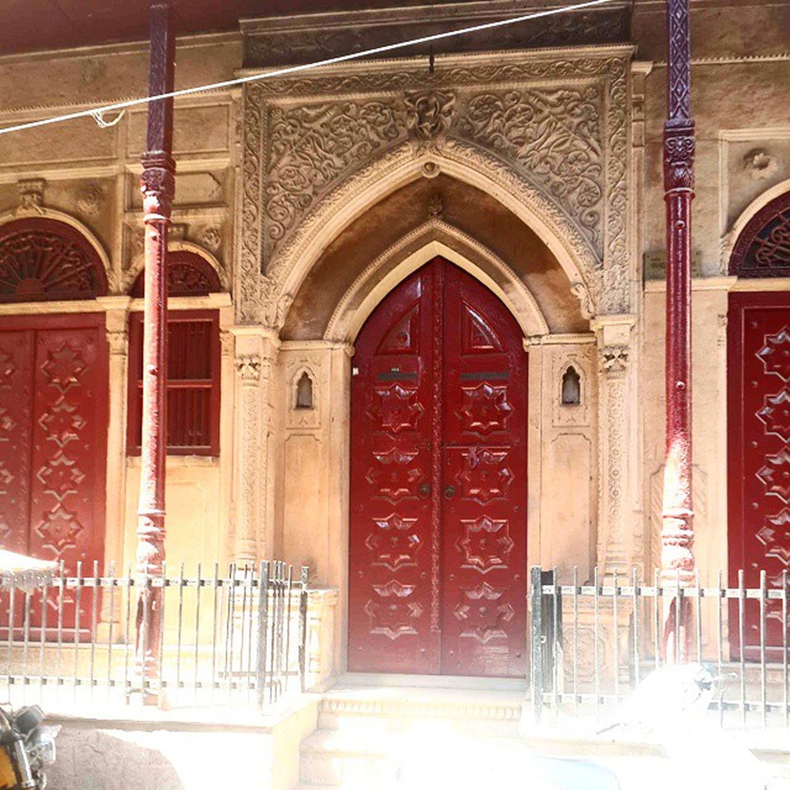 arch, architecture, built structure, indoors, red, door, religion, place of worship, entrance, church, spirituality, closed, wood - material, architectural column, building exterior, day, reflection, window