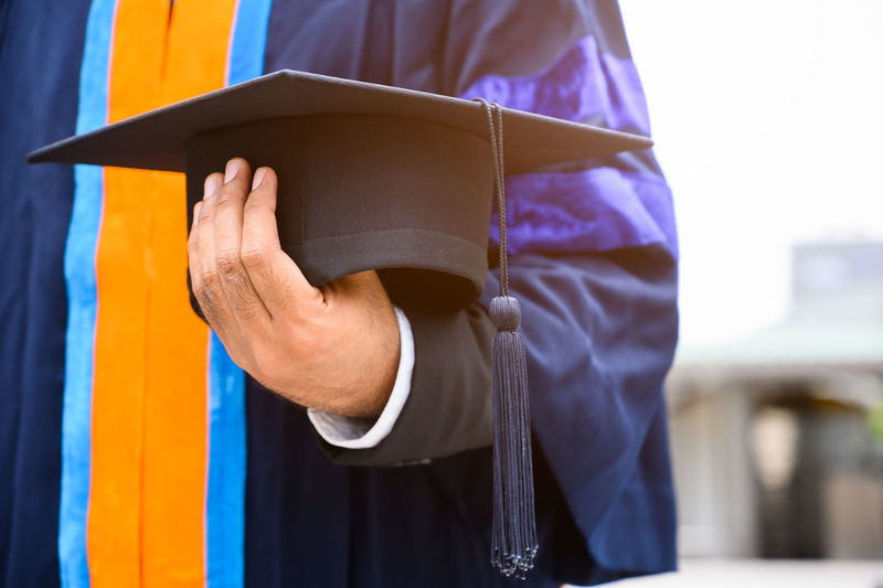 Midsection of man wearing graduation gown holding mortarboard