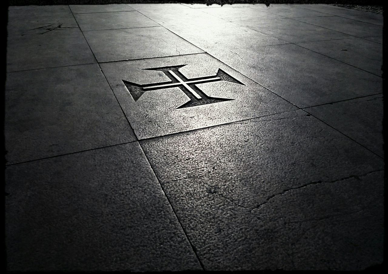 High Angle View Of Cross Shape On Tiled Floor