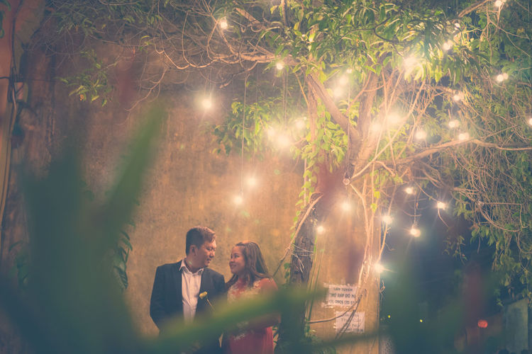 Couple Standing Below Illuminated Lighting Decoration On Tree At Night