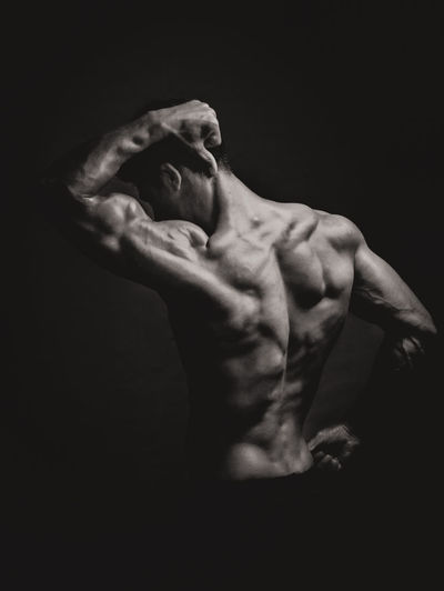 Rear view of shirtless body builder flexing muscles against black background