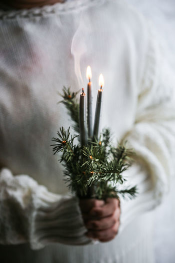 Close-up of woman holding burning candle during christmas