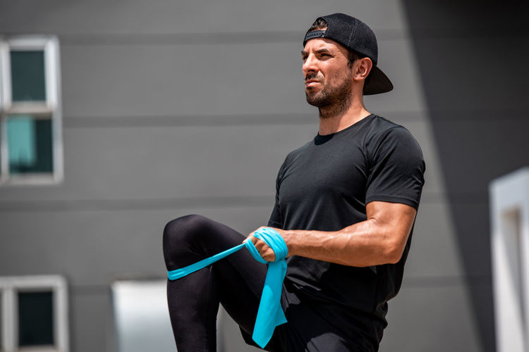 Young man exercising with strap against building