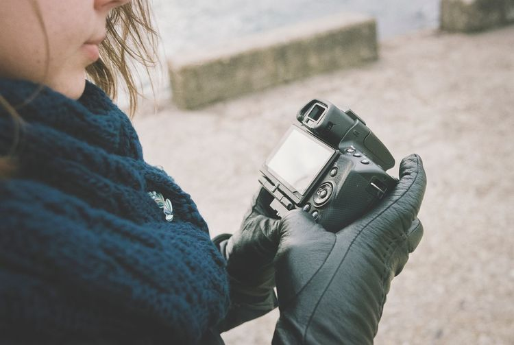 Midsection Of Woman Holding Camera Outdoors