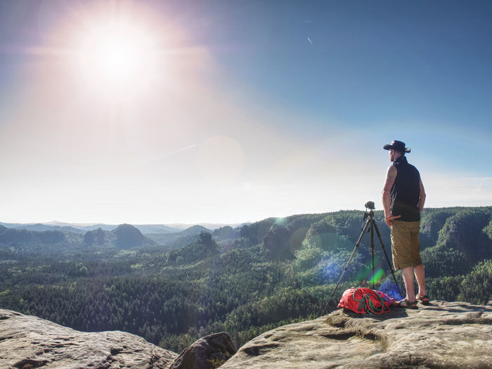 Cowboy hiker at camera on tripod, looking into landscape and thinking. man with leather cowboy hat