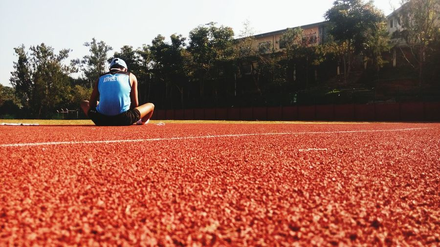 Rear view of athlete sitting on sports track