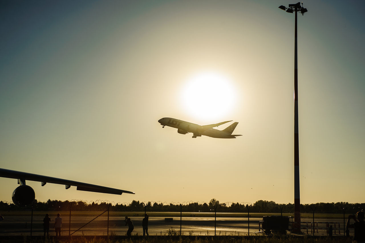 airplane, transportation, flying, sunset, air vehicle, sun, mode of transport, travel, journey, silhouette, clear sky, sky, public transportation, no people, mid-air, outdoors, runway, airport, airport runway, commercial airplane, nature, day