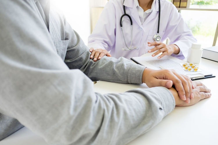 Adult Care Clothing Communication Discussion Doctor  Doctor's Office Expertise Explaining  Healthcare And Medicine Hospital Indoors  Lab Coat Men Midsection Occupation People Professional Occupation Real People Sitting Table Two People Women