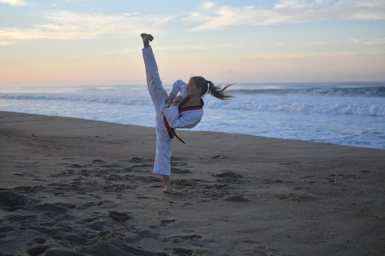 Woman Practicing Karate On Beach Against Sky During Sunset