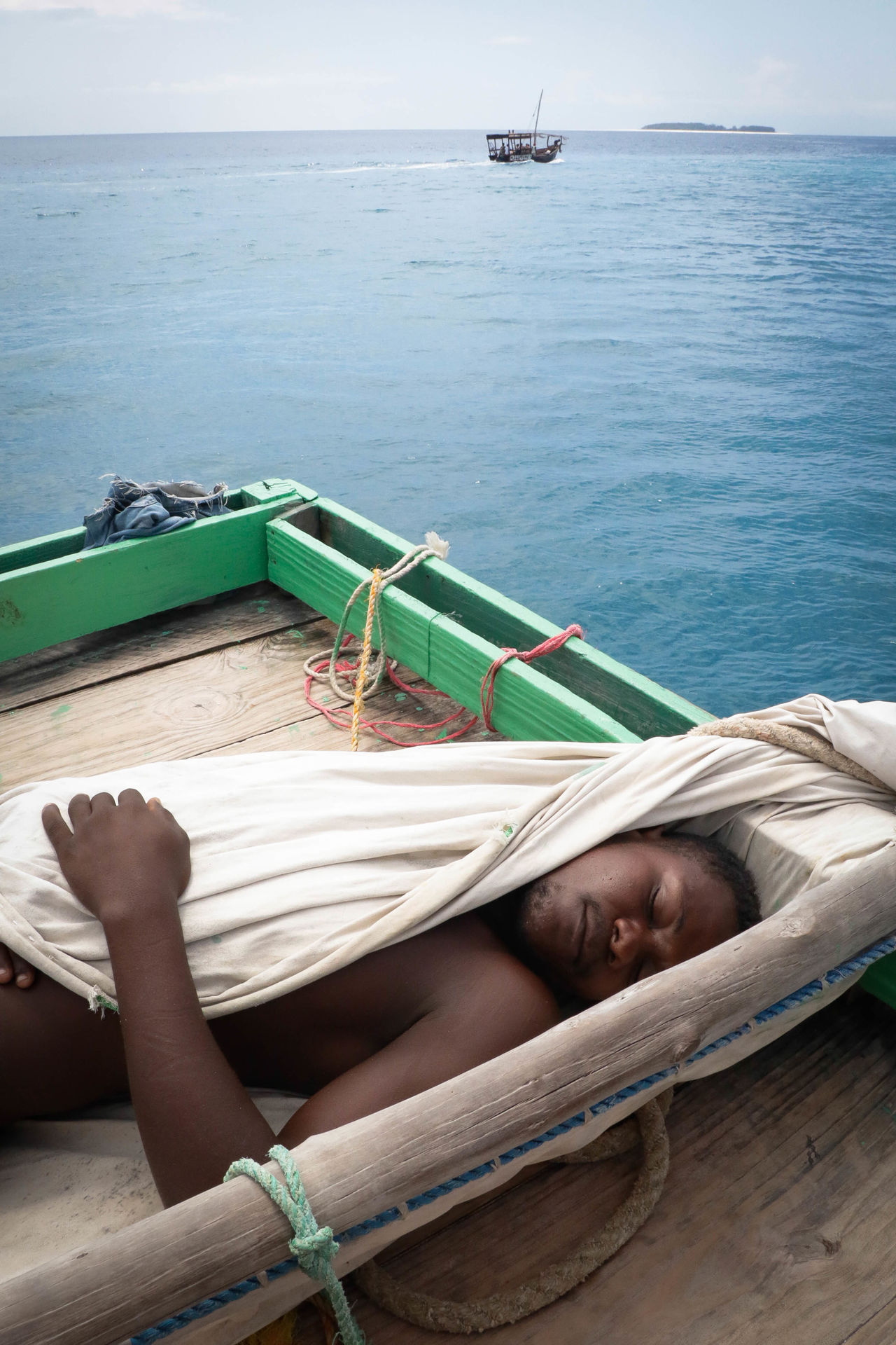 Naked man with blanket sleeping on pier in sea