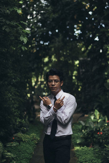 Portrait of young man gesturing while standing on footpath against trees