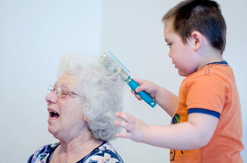 Playful woman with grandson at home