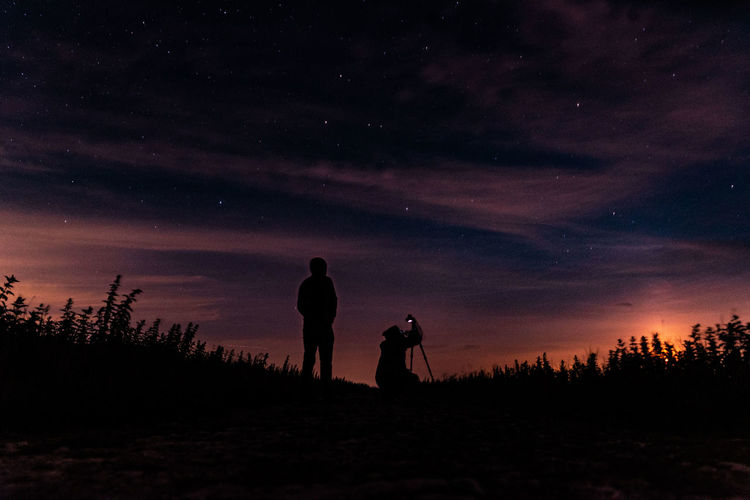 Silhouette men standing on field against sky at night