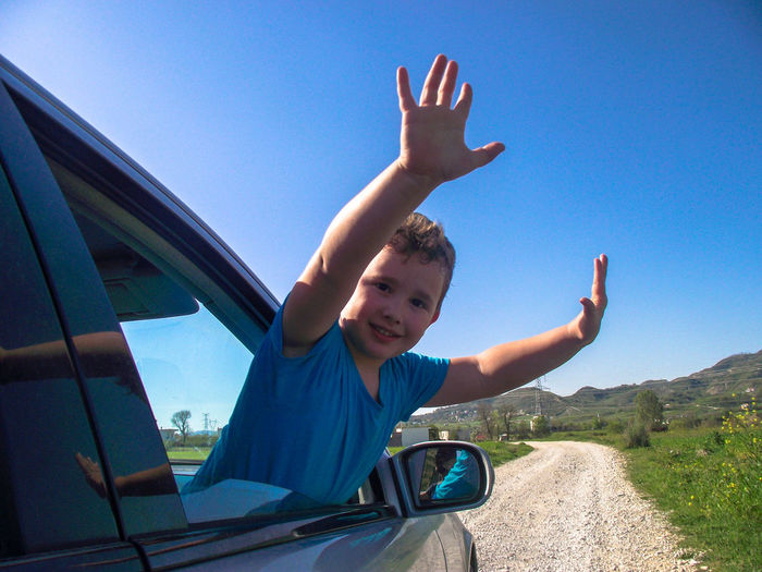 Portrait of boy in car against blue sky