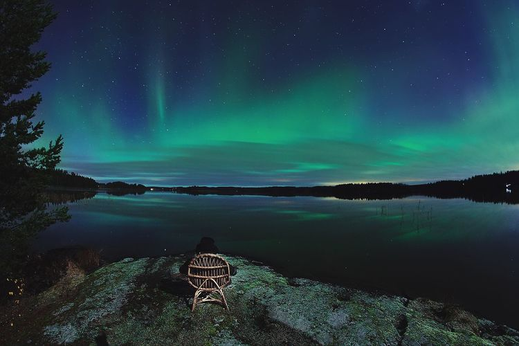 Rear View Of Person Sitting On Chair By Lake Against Aurora Polaris In Sky