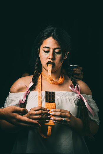 Portrait of woman holding drink against black background