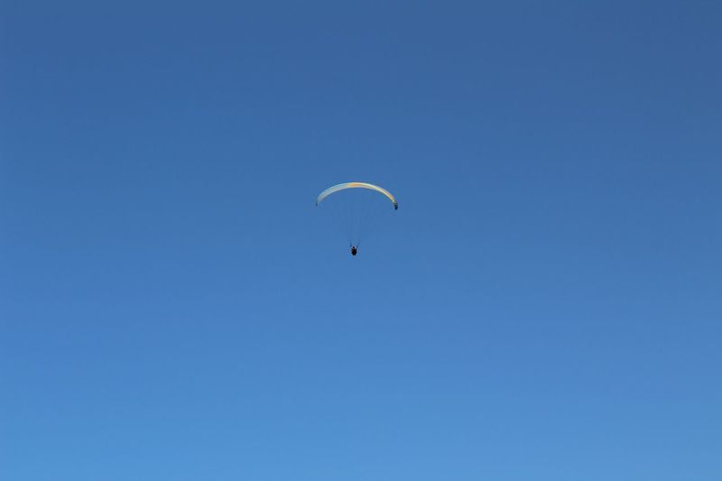 Low Angle View Of Parachute Flying In Clear Blue Sky