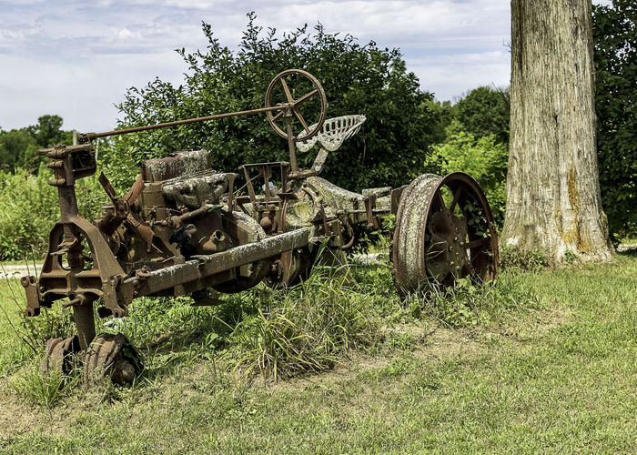An obsolete, rusting, and decaying tractor covered in bird droppings. Field Land Grass Tree Nature Transportation Abandoned Machinery Rusty Wheel Old Obsolete Deterioration Tractor Countryside Country Life Rusting Guano Aged Farming Sky Relic Roadside Agriculture Metal Outdoors