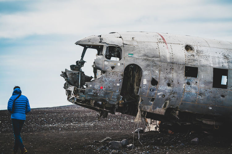 Low angle view of abandoned airplane on airport runway against sky