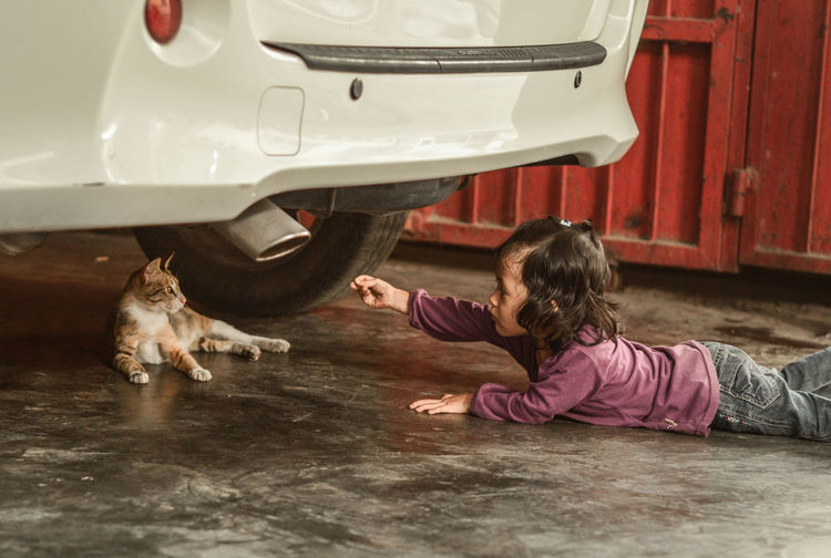 My daughter trying to reach the cat behind the car. INDONESIA Animal Themes Bonding Casual Clothing Cat Close-up Domestic Animals Domestic Cat Friendship Human Hand Indoors  Leisure Activity Lifestyles Mammal One Animal People Pets Playing Real People Young Adult