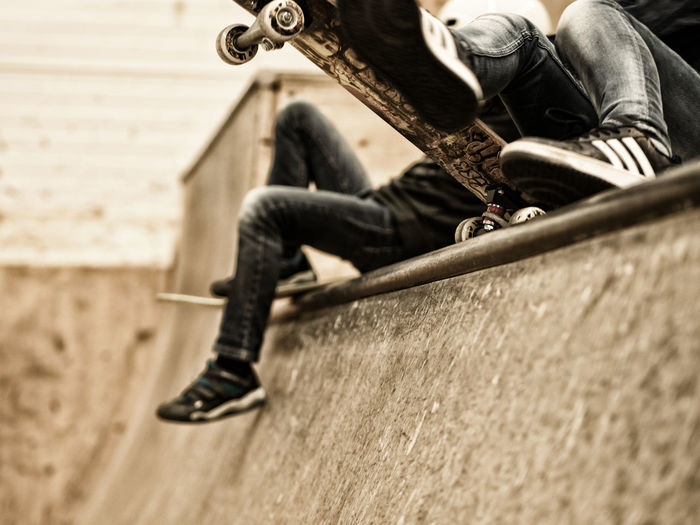 Low Section Of Friends With Skateboards Sitting On Sports Ramp