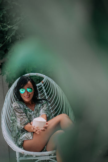 Portrait of woman wearing sunglasses sitting outdoors