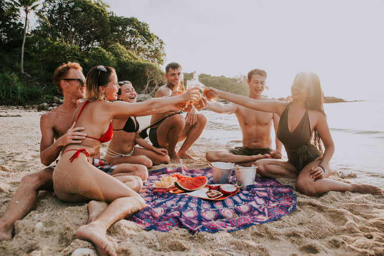 Friends toasting beer bottles while sitting at beach