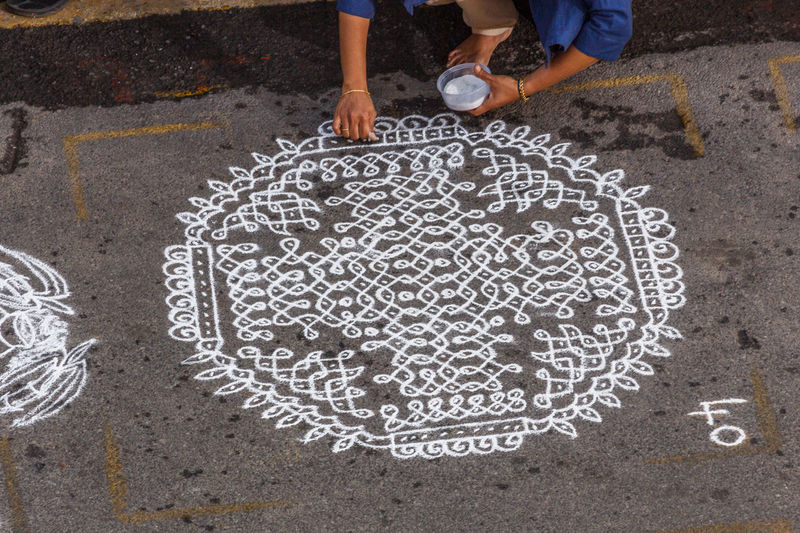 Low section of woman making rangoli on footpath during competition