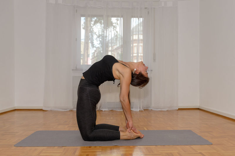 Full length of woman exercising at home