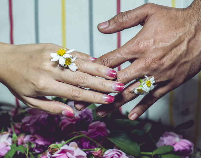 Cropped hands of bride and bridegroom holding white flowers during wedding