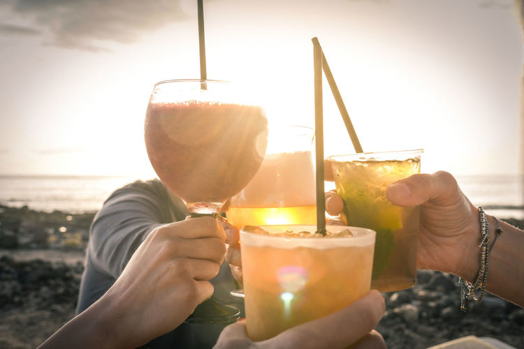Greetings to best friends, group of friends enjoying evening drinks at the beach at sunset. Concept of vacation, carefree, end-of-day relaxation, celebration and well-being. Human Hand Food And Drink Refreshment Holding Hand Drink Human Body Part Glass Real People Women People Two People Lifestyles Alcohol Adult Nature Sky Leisure Activity Food Candle Outdoors Cocktail