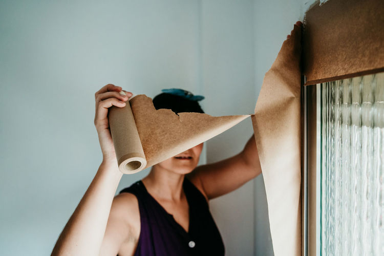 Woman holding cardboard paper working by window at home