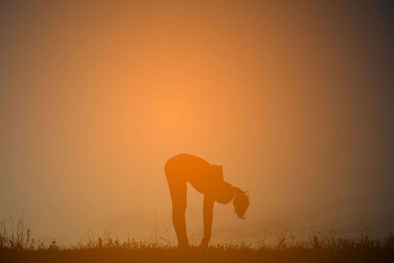 Silhouette woman practicing yoga on field against sky during sunset